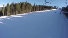 Een skilift vervoert omhoog mensen op de berg De skiërs dalen van de sneeuwbergen De mensen ski?en, hoge sparren stock video