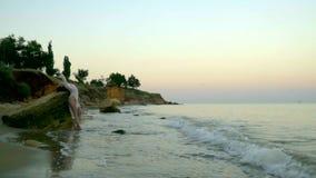 Een slank blonde met lang haar in een mooie witte kleding bevindt zich bij een rots in een schilderachtige baai, op de rand van e stock footage