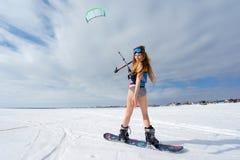 Een slank meisje in een badpak in de winter Snowboarding en Stock Foto