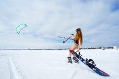 Een slank meisje in een badpak in de winter Snowboarding en Stock Fotografie