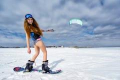Een slank meisje in een badpak in de winter Snowboarding en Royalty-vrije Stock Afbeelding
