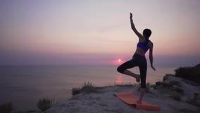 Een slank meisje probeert om yoga, moeilijkheden te leren in het beheersen van de de yogahouding en mislukking Sport bij zonsopga stock footage