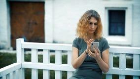 Een slanke droevige vrouw op middelbare leeftijd met krullend blond haar zit op een witte bank in de avond en bekijkt de telefoon stock videobeelden