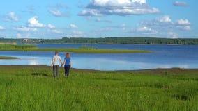 Een slanke man en een vrouw lopen langs de handen van de kustholding stock videobeelden