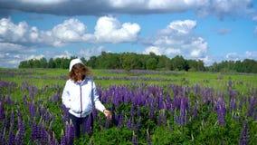 Een slanke mooie vrouw, gangen door de weide onder de purpere bloemen en glimlachen op een Zonnige dag stock videobeelden