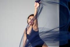 Een slanke turner in zwarte legging danst met een blauwe chiffon die zich ontwikkelt Esthetica van dans royalty-vrije stock fotografie