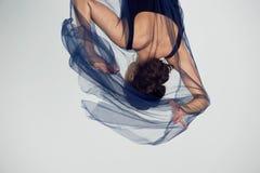 Een slanke turner in zwarte legging danst met een blauwe chiffon die zich ontwikkelt Esthetica van dans stock foto