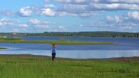Een slanke vrouw in een bovenkledij loopt aan de rivierbank op het groene gras, op een Zonnige dag en heft gelukkig haar handen a stock video