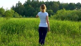 Een slanke vrouw loopt blootvoets op een groene weide met roze klaverbloemen op een zonnige de zomerdag stock video