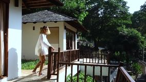 Een slanke vrouw stalt op het terras uit tegen de achtergrond van groene bladeren op een warme Zonnige de zomerdag stock videobeelden