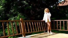 Een slanke vrouw in een wit overhemd bevindt zich op het terras en glimlacht op een Zonnige de zomerdag stock videobeelden
