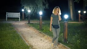 Een slanke, zoete vrouw op middelbare leeftijd met krullend blond haar loopt onderaan een groene steeg met lantaarns op een de zo stock video