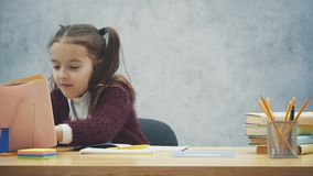 Een slim schoolmeisje zit bij de lijst en schrijft thuiswerk Tijdens dit zoekt de pagina in het boek stock video