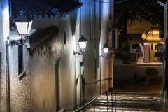 Een smalle straat met treden en lantaarns op de muur bij nacht in Pylos, Griekenland royalty-vrije stock foto
