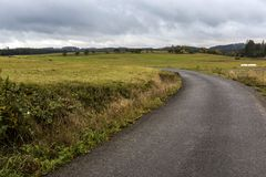 Een smalle weg die tussen gebieden onder onweerswolken leiden Royalty-vrije Stock Foto