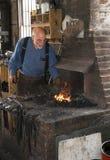 Een smid die zwart metaal in een winkel historische van de 100 éénjarigen (smidse) werken smid in Loodglans Stock Afbeelding