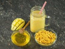 Een smoothie van mango, banaan, honing en graangewas op een zwarte steenlijst Een kom honing en kom graangewas Stock Fotografie