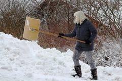 Een sneeuw van vrouwenschoppen in de winter Sneeuwschoppen tijdens sneeuwval royalty-vrije stock afbeelding