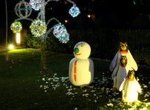 Een sneeuwman en drie kwade pingu?nen bevinden zich op een groen gazon Sneeuwman met een groene neus Kerstmisviering in landen me royalty-vrije stock afbeelding