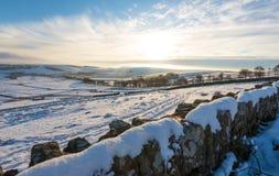 Een sneeuwmuurlijnen de mening van een mooie koude zonsondergang in het Piekdistrict stock foto