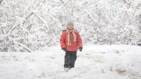 Een sneeuwstorm in December De jongen in een sneeuwbos stock videobeelden