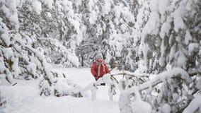 Een sneeuwstorm in December De jongen in een sneeuwbos stock footage
