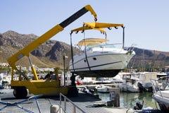 Een snelheidsboot die in het overzees door een kraan worden verminderd Stock Fotografie