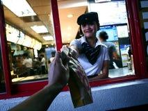 Een snelle voedselketenarbeider geeft een klant een gekocht product door bij een aandrijving stock foto's