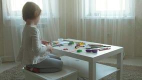 Een snijdt de kleine meisjesspelen met plasticine, met schaar in stukken, liggen de cijfers en de kleurpotloden op de Desktop, stock footage