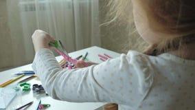 Een snijdt de kleine meisjesspelen met plasticine, met schaar in stukken, liggen de cijfers en de kleurpotloden op de Desktop, stock videobeelden