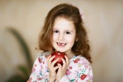 Een snoepje weinig krullende tand met bruine ogen het meisje glimlacht en houdt in haar handen een rode appel die melktanden heef stock afbeeldingen