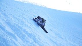 Een snowboarder die een berghelling beklimmen stock footage