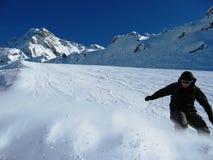 Een Snowboarder die omhoog poeder op een piste schoppen Stock Foto's