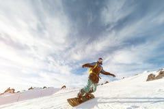 Een snowboarder in een skimasker en een rugzak berijdt op een snow-covered helling weggaand achter een sneeuwpoeder tegen Royalty-vrije Stock Foto