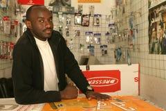 Een Soedanese vluchteling in zijn mobiele telefoonwinkel royalty-vrije stock foto