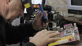 Een soldeerbout in zijn handen stock videobeelden
