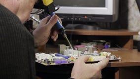 Een soldeerbout in zijn handen stock video
