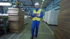 Een specialist loopt langs de fabriekseenheid met dozen en plastiek wordt gevuld dat stock videobeelden