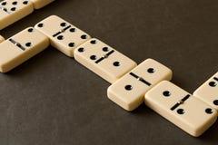 Een spel van domino's op een donkere lijst Het concept het spel van stock fotografie