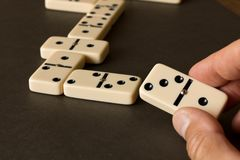 Een spel van domino's op een donkere lijst Het concept het spel van domino's Mensen` s hand met een Domino Sluit omhoog royalty-vrije stock afbeeldingen
