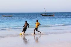 Een spel van voetbal op het strand bij zonsondergang Stock Foto