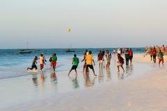 Een spel van voetbal op het strand bij zonsondergang Stock Afbeelding