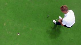 Een speler raakt een bal in een gat op een golfing gebied stock footage