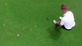 Een speler raakt een bal in een gat op een golfing gebied stock video