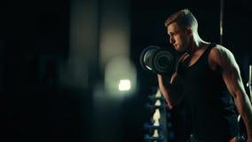 Een spiermens voert oefeningen uit begrijpt domoren voor spieren van de bicepsen die in een donkere gymnastiek, gewichten opheffe stock footage