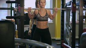 Een spiervrouw in een elastisch kostuum crouches met een barbell in een sportclub stock footage