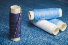Een spoel van blauwe draden met een naaiende naald op de achtergrond van spoelen van blauwe en witte draden op een denimstof royalty-vrije stock afbeelding