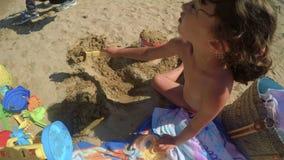 Een spontaan kind speelt op het strand met emmer en spade 2 FDV stock video