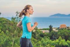 Een sportieve jonge vrouw is bezig geweest met het lopen tegen het overzees royalty-vrije stock afbeeldingen