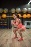 Een sportieve vrouw die roze sportenkostuum en trainers dragen doet het hurken in een gymnastiek Aëroob en geschiktheidsconcept stock afbeelding